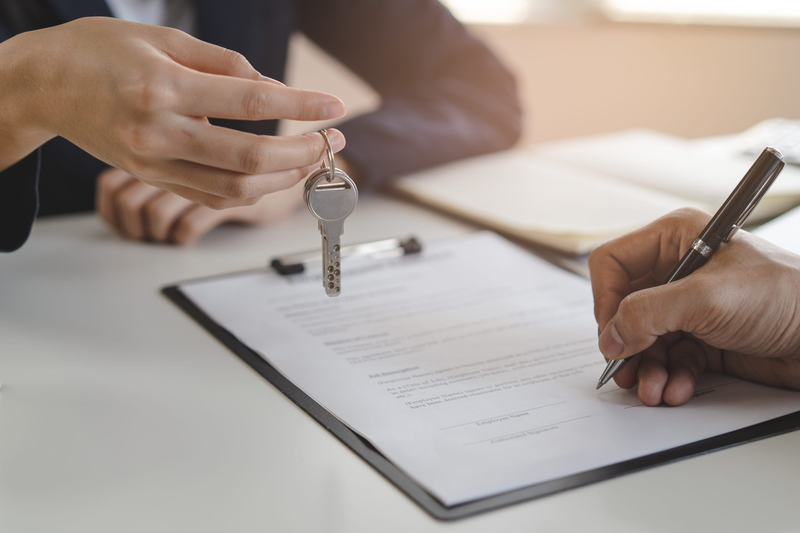 landlord giving a house keys to tenant after signed rental contract.