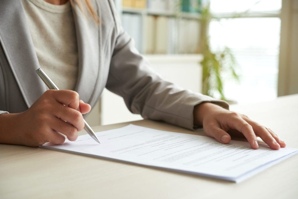 Hands of business entrepreneur signing document on her table